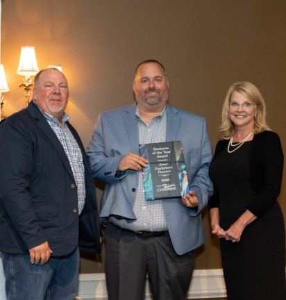 Photo is of three individuals, with Todd Wainwright in the middle holding the Business of the year award. In the background there is a banner with the Chamber and event logo.